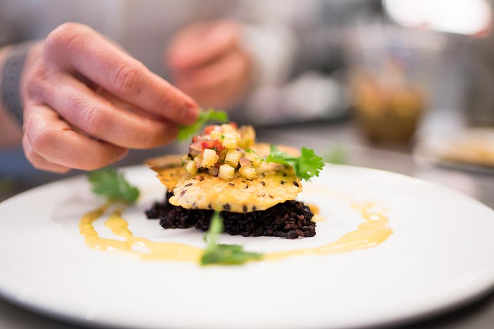 Chef Barbara Rich plates seared tempeh with cilantro.